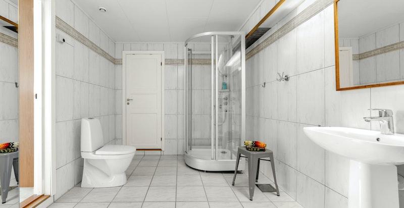 Romslig flislagt bad med adkomst fra soverom. Dør inn til lagringsbod