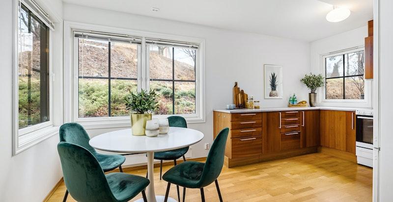 Stort kjøkken med spiseplass og vinduer på tre sider