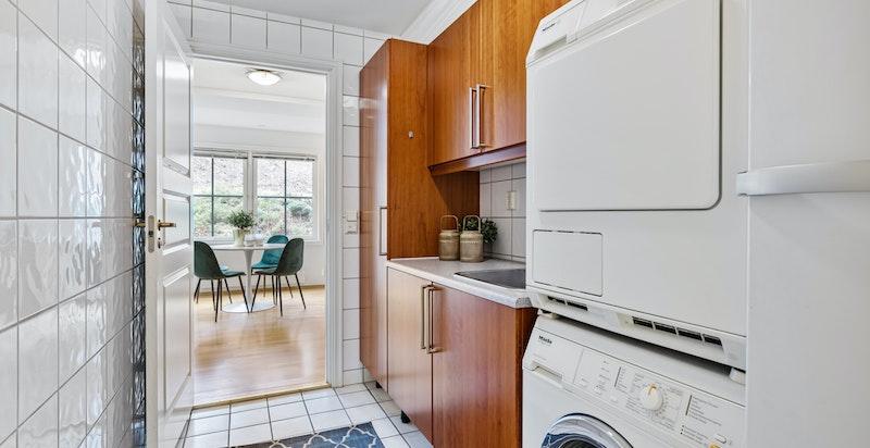 Praktisk vaskerom vis a vis kjøkkenet med opplegg for vaskemaskin, tørketrommel og ekstra kjøl/ frys.