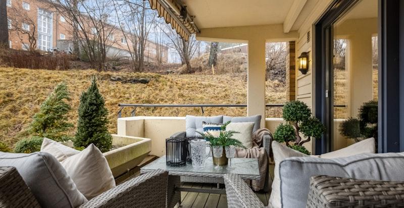 Herlig, solrik og skjermet terrasse i grønne omgivelser.  Dype plantekasser gir en grønn innramming.