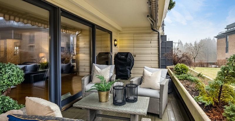 Herlig, solrik og skjermet terrasse i grønne omgivelser. I enden er det en praktisk utebod til uteputer mv.