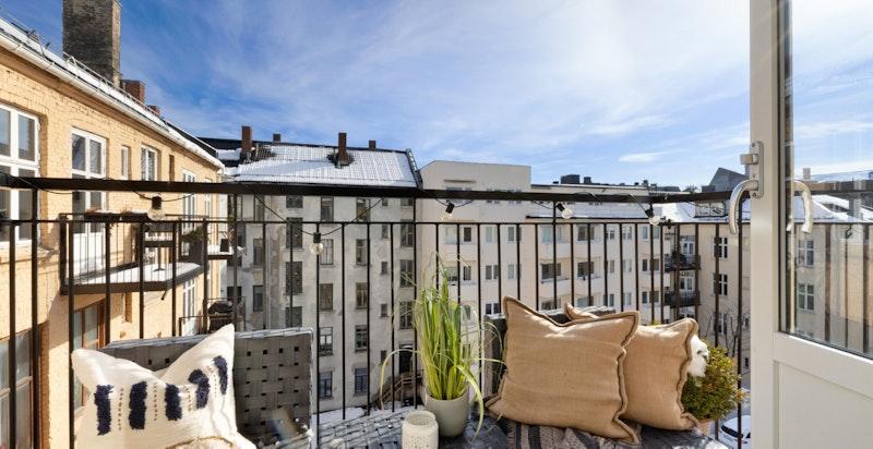 Luftig balkong mot den romslige bakgården. Tidlig morgensol