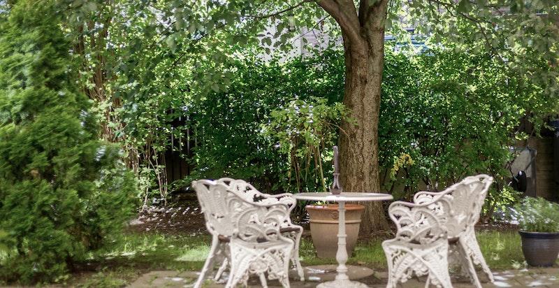 Hyggelig bakgård med sittegrupper og trær - sommerstemning