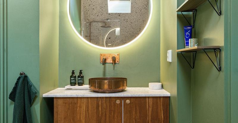 Badet har stilfulle fargekombinasjoner, varmekabler i gulvet og praktiske detaljer.