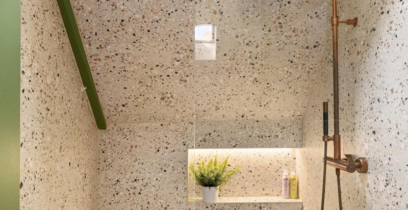 Badet er utstyrt med dusj i hjørne med glassvegg. Den innebygde hyllen er både en flott detalj og svært praktisk.
