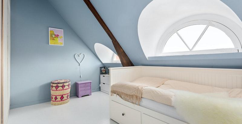 Rommet er malt i en behagelig blåtone og har to klassiske bueformede vinduer.