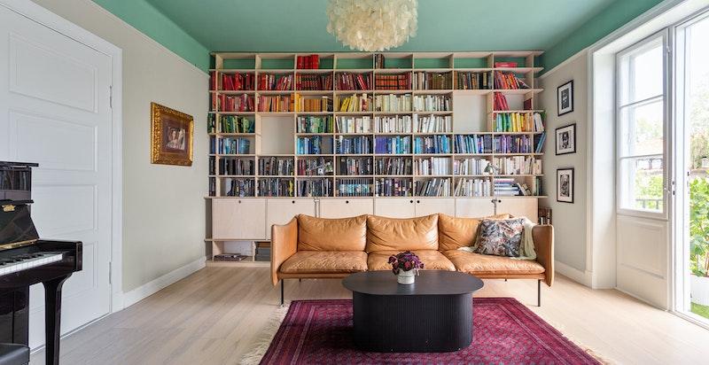 Flott og plassbygget bokhylle med en blanding av store og små hyller, samt skap for ekstra oppbevaring.