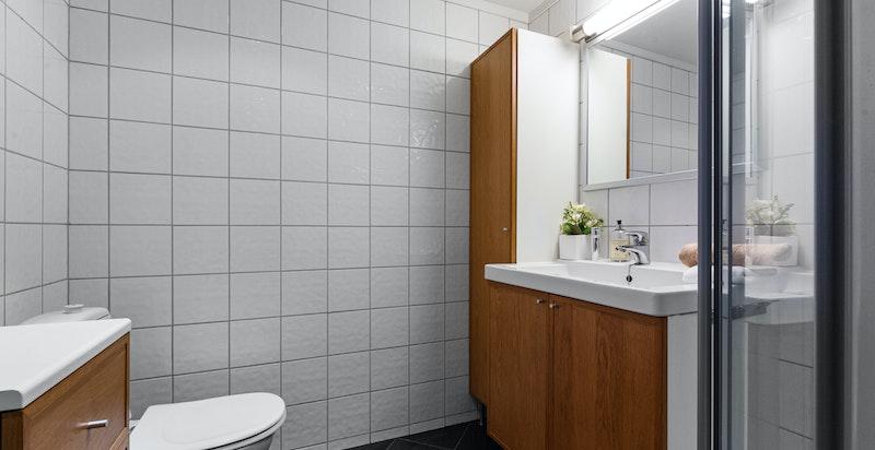 Badet har flislagt gulv med varmekabler og flislagte vegger