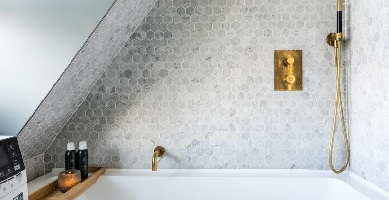Badet er utstyrt med dusj i badekar, veggehengt wc og opplegg for vaskemaskin.