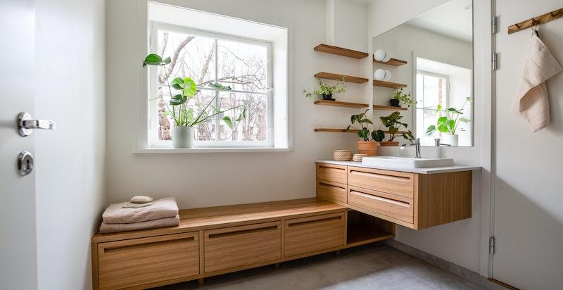 Badet har varmekabler i gulv og inneholder dusjhjørne med innfellbare dusjdører/glassdører, veggmontert toalett, servant med snekkertilpasset baderomsmøbel og blandebatteri på kompositt benkeplate