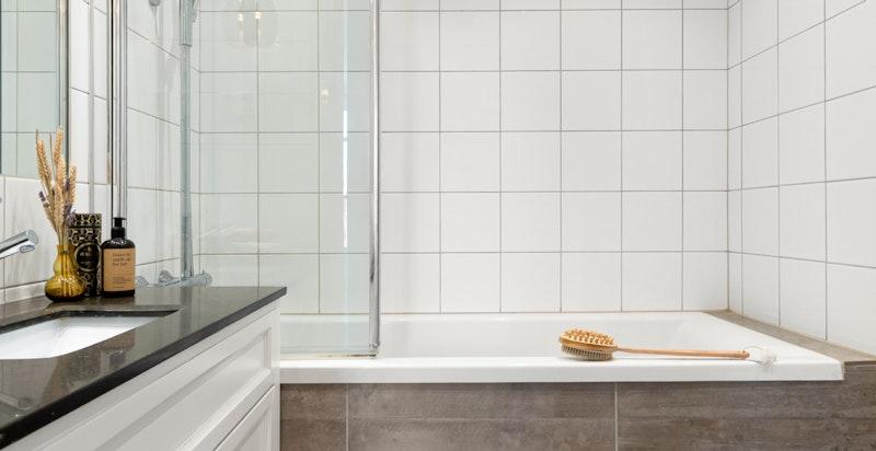 Innmurt badekar med glassvegg. Inspeksjonsluke bak flispanelet.