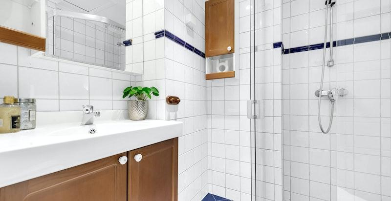 Dusjbad/wc med varmekabler i gulv. Badet består av dusjhjørne med skyvedør, toalett, servant med underskap og blandebatteri. Elektrisk avtrekksvifte til original kanal