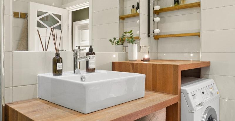 Bad med vegghengt wc, servant i eik innredning, dusj i hjørne med innadslående dører og opplegg for vaskemaskin.