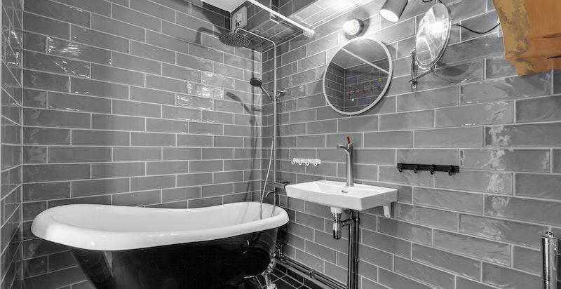 Badet er innredet med servant, ett greps blandebatteri, speil, belysning og hyller.