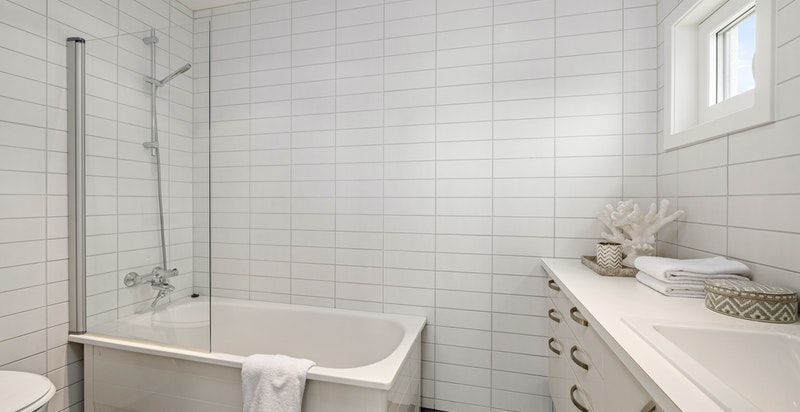 Tidløst flislagt bad med badekar inn fra hovedsoverom