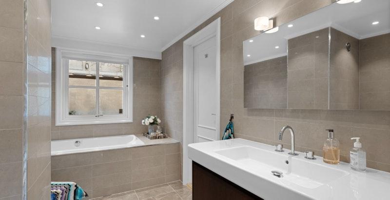 Hovedbadet med badekar, servantskap med helstøpt benkeplate/servant, vegghengt wc