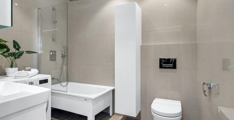Badet inneholder frittstående badekar, veggmontert wc, elektrisk avtrekksvifte, servant med underskap og blandebatteri. Opplegg til vaskemaskin
