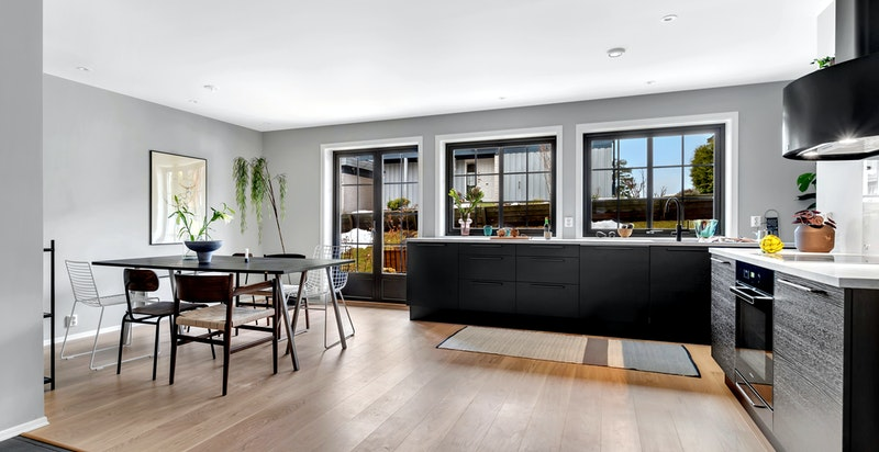 - Rommet har flere vinduer med slanke profiler, sprosser i sort og dype karmer som gir en flott kontrast til de ellers lyse overflatene -