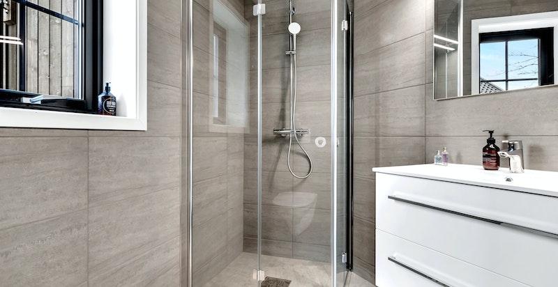 - Bad innredet med baderomsinnredning med skuffer og heldekkende servant, dusjhjørne med svingbare glassdører og vegghengt toalett -