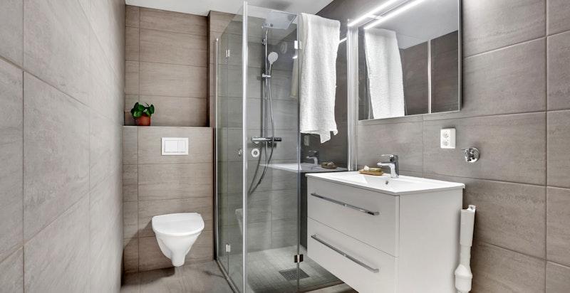 - Lekkert bad i kjeller innredet med servantskap med heldekkende vask, speil med lys, vegghengt toalett og dusjhjørne med glassdører -