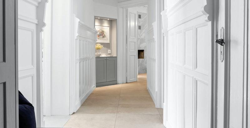 Mellomgangen er innbydende og langstrakt med tilknytning til boligens andre baderom.