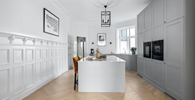 Kjøkkenet ligger i en praktisk og fin løsning fra spisetuen med en delikat og snekkerbygget innredning.
