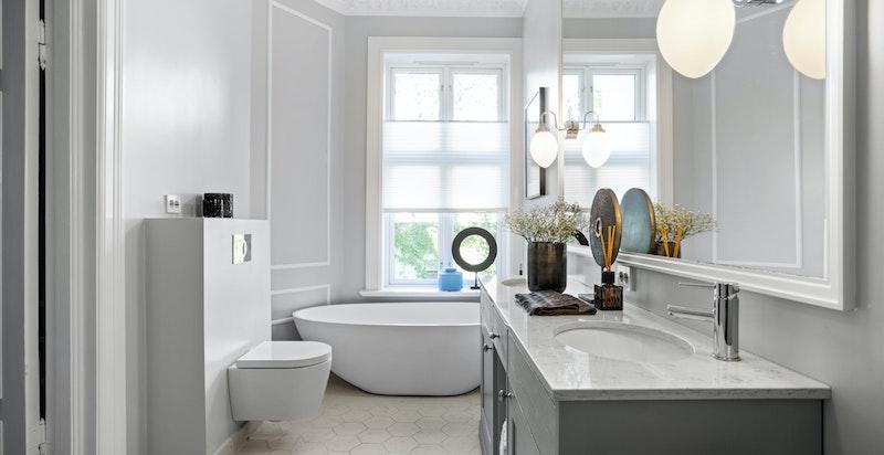 Badet er utstyrt med vegghengt wc, to servanter med flott snekkerbygget innredning og kvarts benkeplate. Badet har i tillegg et nydelig badekar.
