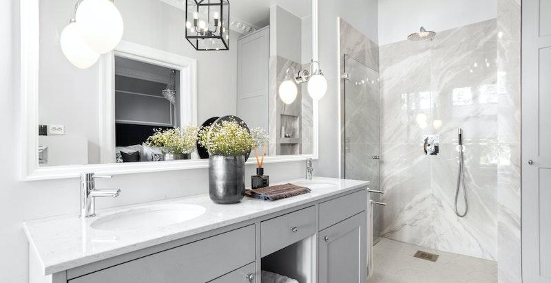 Badet er romslig, og utstyrt med praktisk dusj i hjørnet med glassdør. Det er vaskemaskin og tørketrommel i innebygget skap.