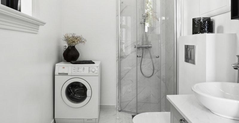 """Badet er utstyrt med vegghengt wc, servantinnredning i """"skål"""" med skuffer under og dusj i hjørnet med innadslående dører. I tillegg er det opplegg for vaskemaskin og tørketrommel."""
