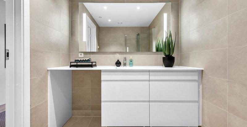Flott innredning og stort speil med integrert belysning. Opplegg til vaskemaskin under benk.
