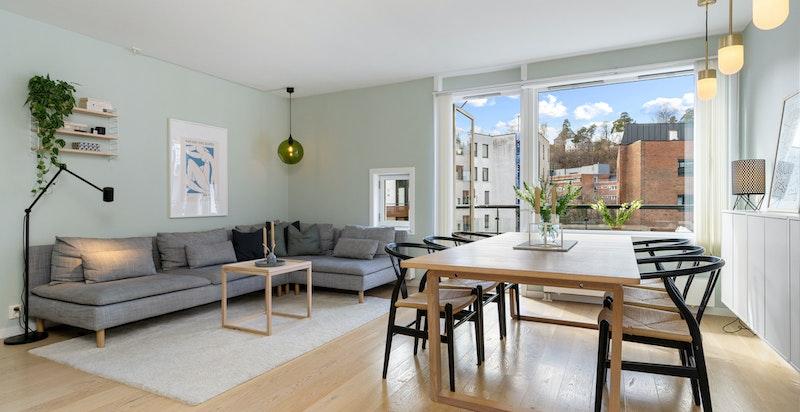 Overblikk stue med salong og spisestuen. Utgang til balkong i bakgrunnen