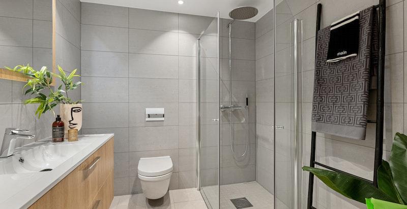 Badet er påkostet med baderomsinnredning og speil.