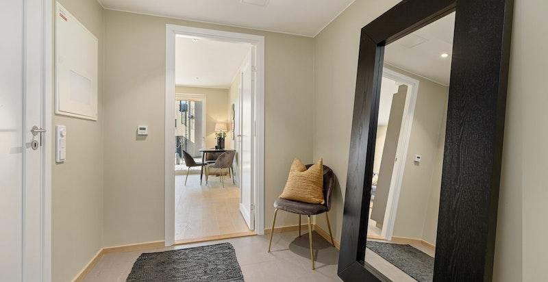 Entreen gir et godt førsteinntrykk med gulvfliser, downlightsbelysning og delikat fargevalg på veggene.