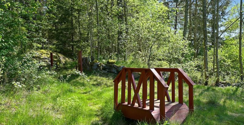 Eiendommen har en liten rød bro over en liten bekk. En skogssti fører over broen og over øvre del av eiendommen (kun enkelte lokale som ferdes her i ny og ne)