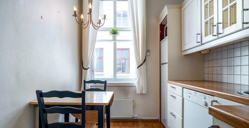 Kjøkken med hvitevarer og spisebord