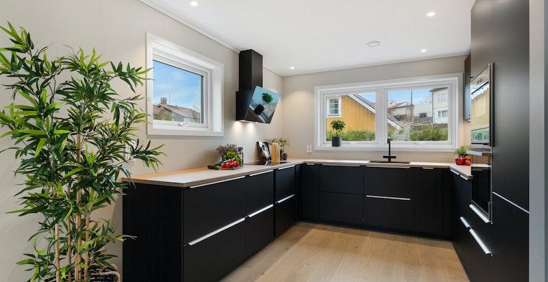 Moderne kjøkkeninnredning med sorte glatte fronter og mye benkeplass