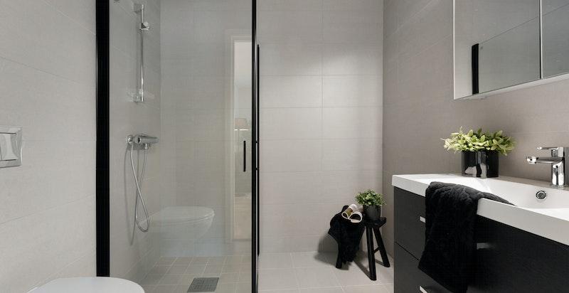 Moderne bad i u.etg. innredet med innfellbare dusjdører, servantskap og vegghengt toalett
