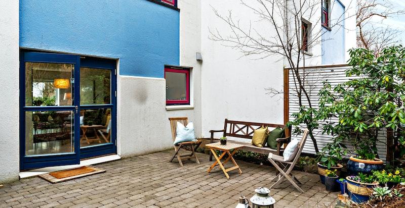 Her fra uteplassen utenfor kjøkkenet. Lun og hyggelig plass for morgenkaffen.