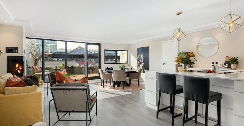 Stue med åpen kjøkkenløsning, peis og utgang til terrasse