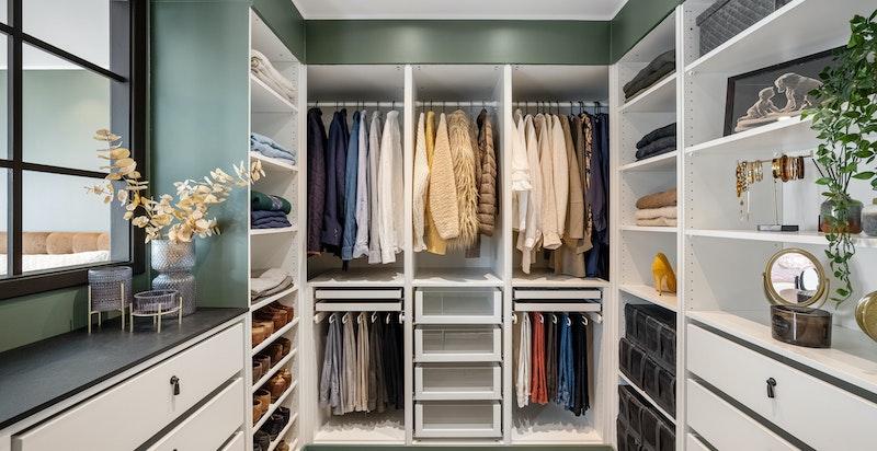 Delikat og praktisk innredet walk-in garderobe med heng, hyller og skuffer for effektiv oppbevaring