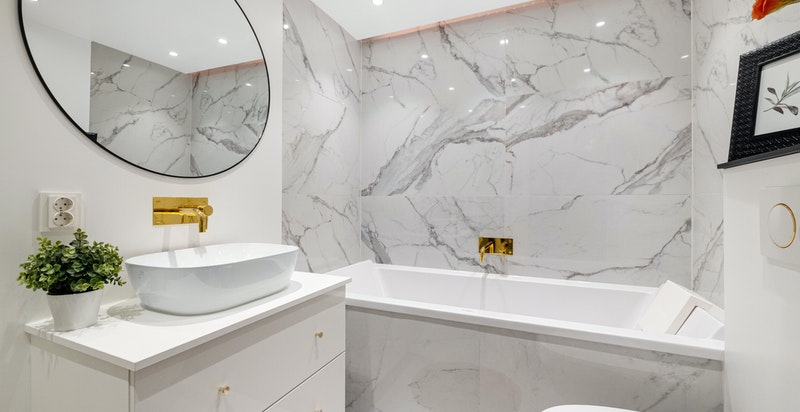 Lekkert bad med dusjhjørne, badekar, toalett og servantinnredning
