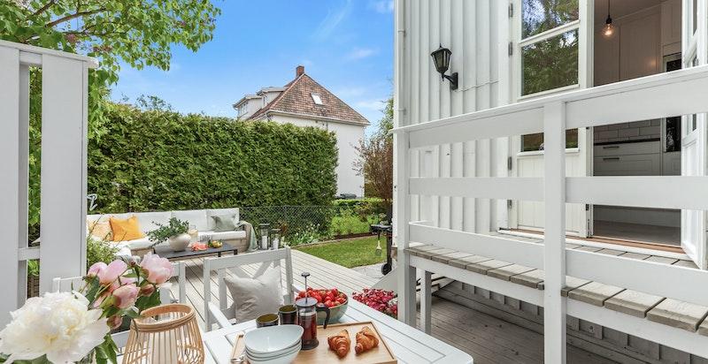 Utgang fra kjøkken til solrik terrasseplatting fra 2014 med levegg og utesofa