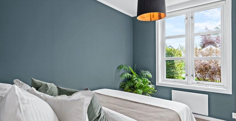 Pent soverom med stort vindu ut mot grøntarealer. Overflater ble pusset opp i 2021