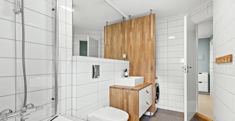Badet inneholder innmurt badekar, veggmontert toalett, servant fra 2021 med underskap og blandebatteri på heltre benkeplate