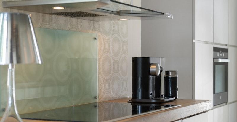 Over kjøkkenbenken/koketopp er det ventilator og glassplate