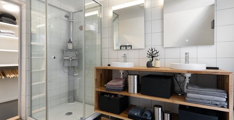 Badet har varmekabler i gulvet og har både dusjkabinatt og badekar, veggmontert klosett og servant i underskap