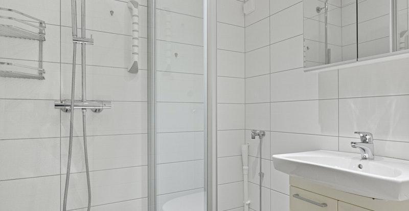 Badet er utstyrt med baderomsinnredning over heldekkende servant, ettgreps blandebatteri og speilskap.