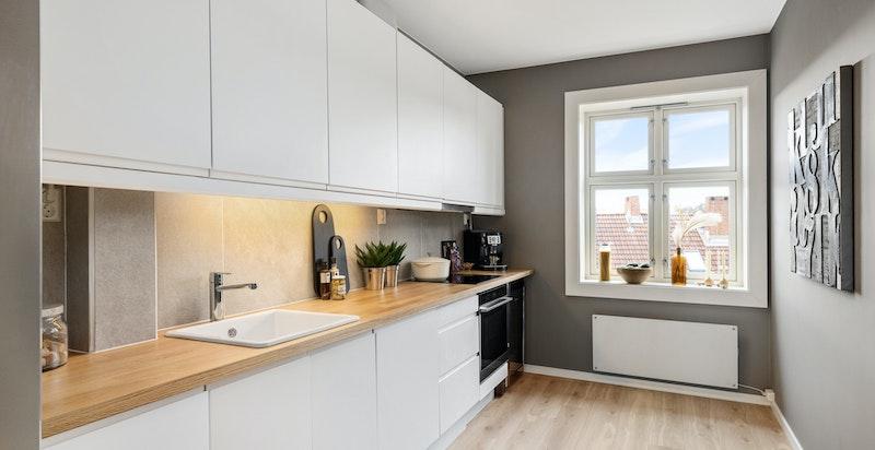 Pent kjøkken med ny innredning i 2021. Hyggelig utsikt til en av de to store bakgårdene i borettslaget
