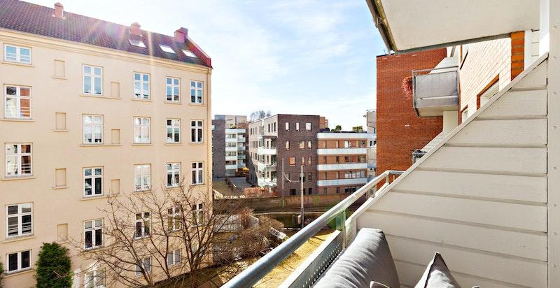 Sydvendt overbygget balkong mot bakgård.