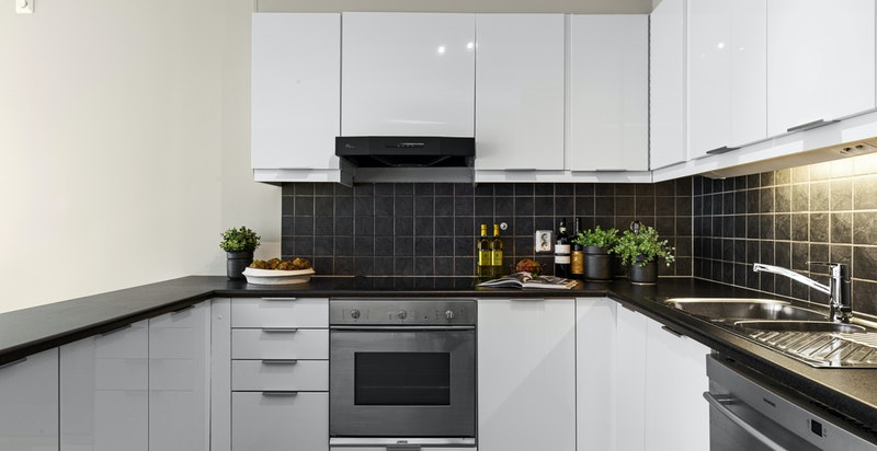 Lekkert U-kjøkken med kjøkkenøy og rikelig med lagringsplass og benkeplass